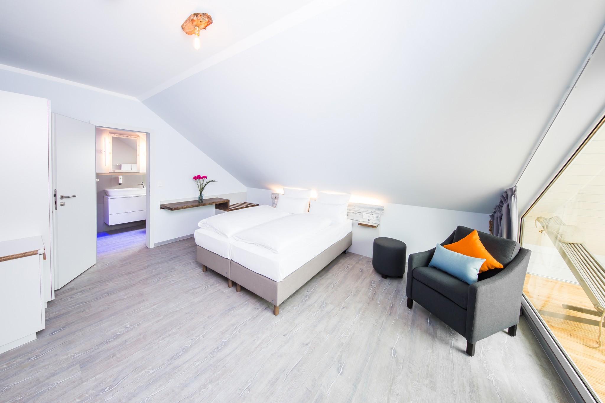 Doppelbett, Bad und Balkon in hellem Hotelzimmer